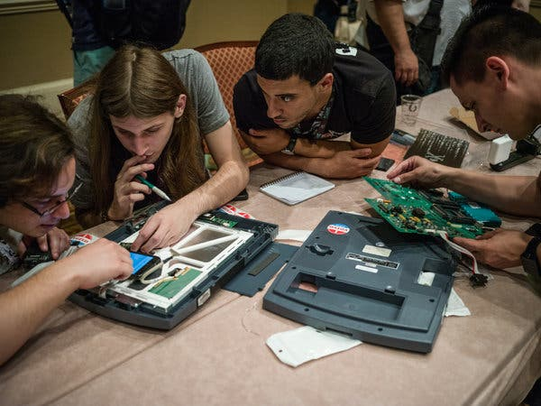 Hackers examining a voting machine at the DefCon cybersecurity conference in Las Vegas in 2017.